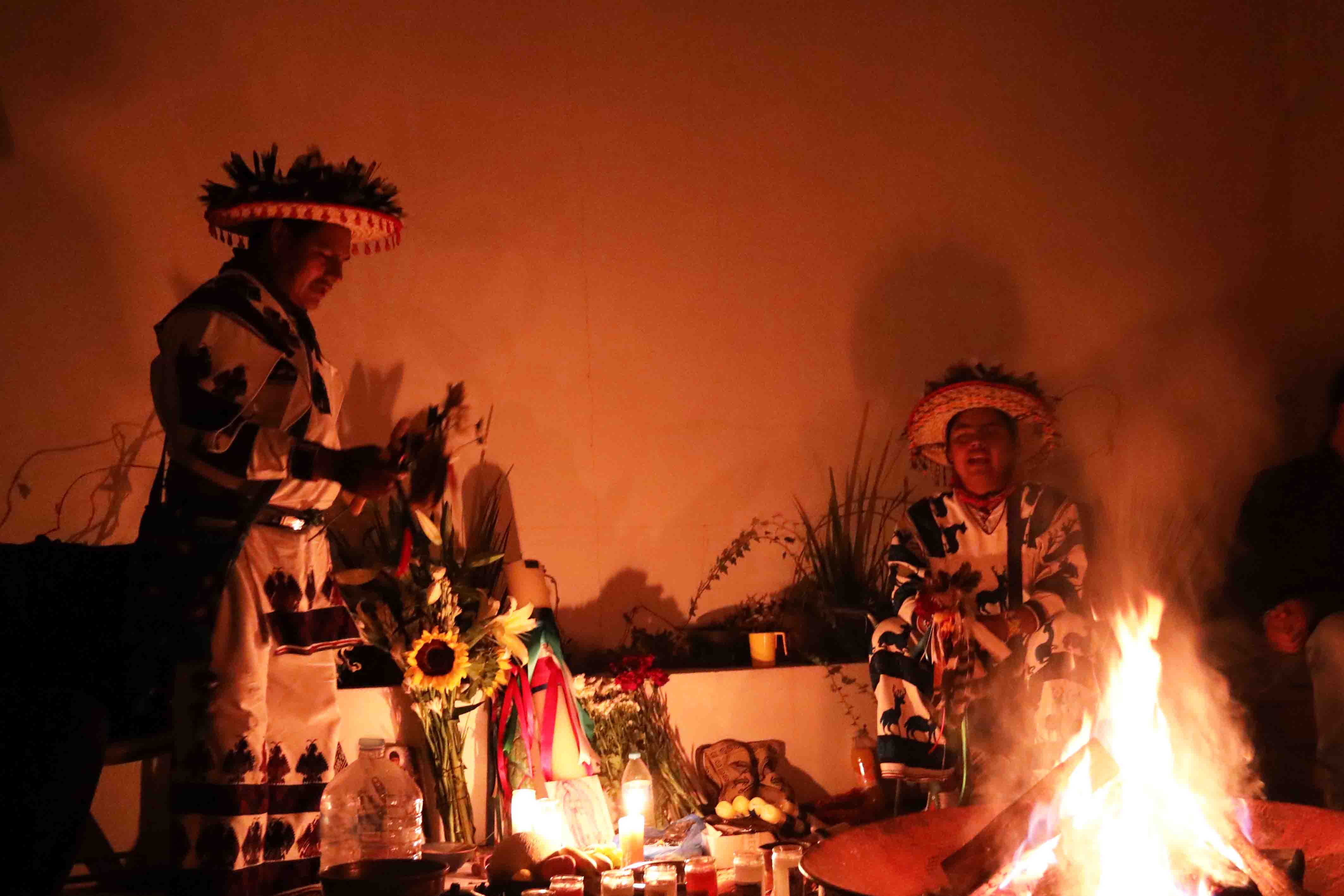 Two Huichols singing traditional wixárika songs with a campfire, in their typical costumes, against a background of plants, flowers and an altar.