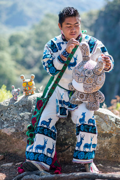 Huichol artist making a Dunny piece of art from Kidrobot in a landscape of the Sierra Madre Occidental