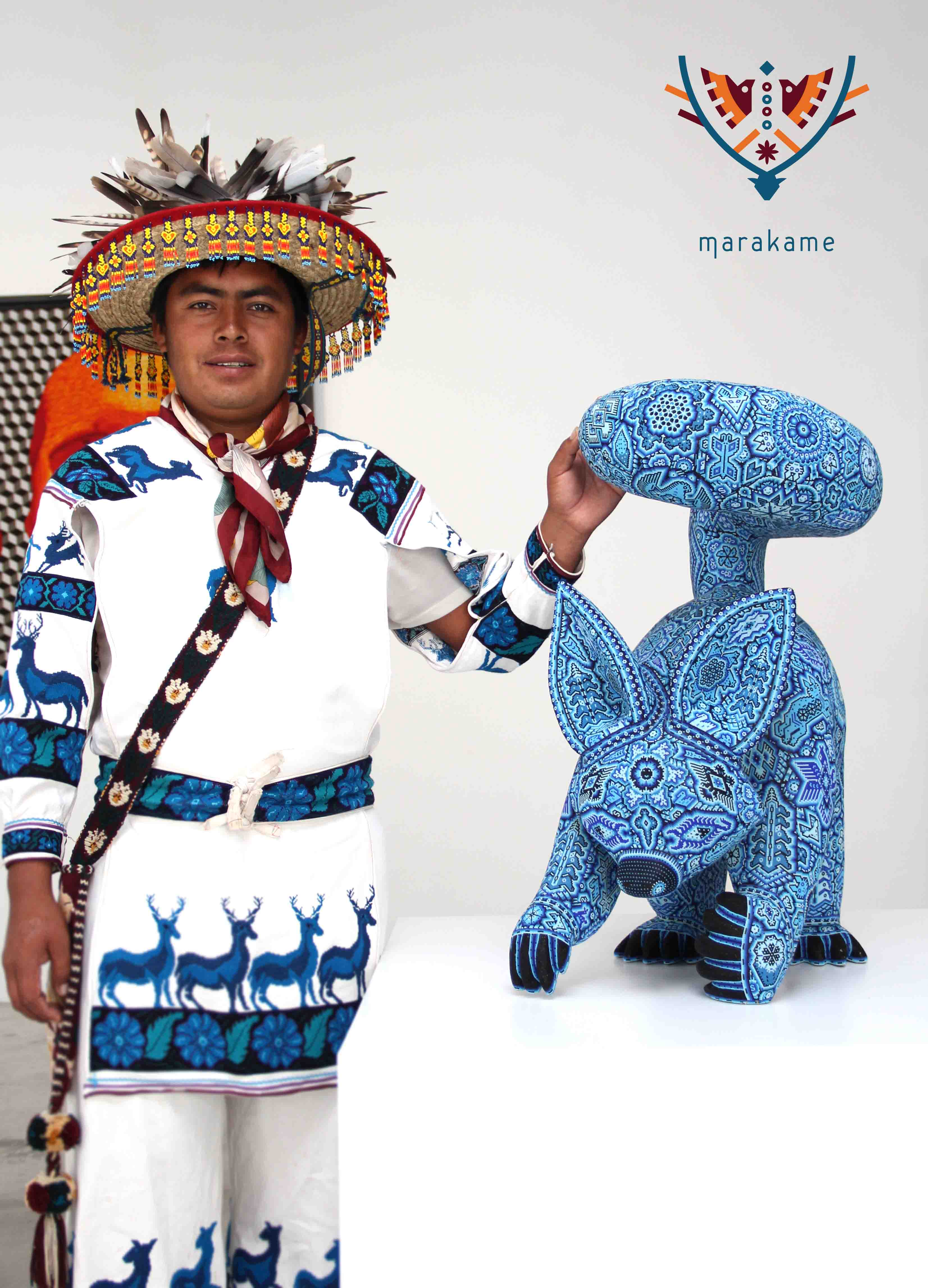 Large-format wooden sculpture of a fox in blue beads, with the artist Sergio Bautista