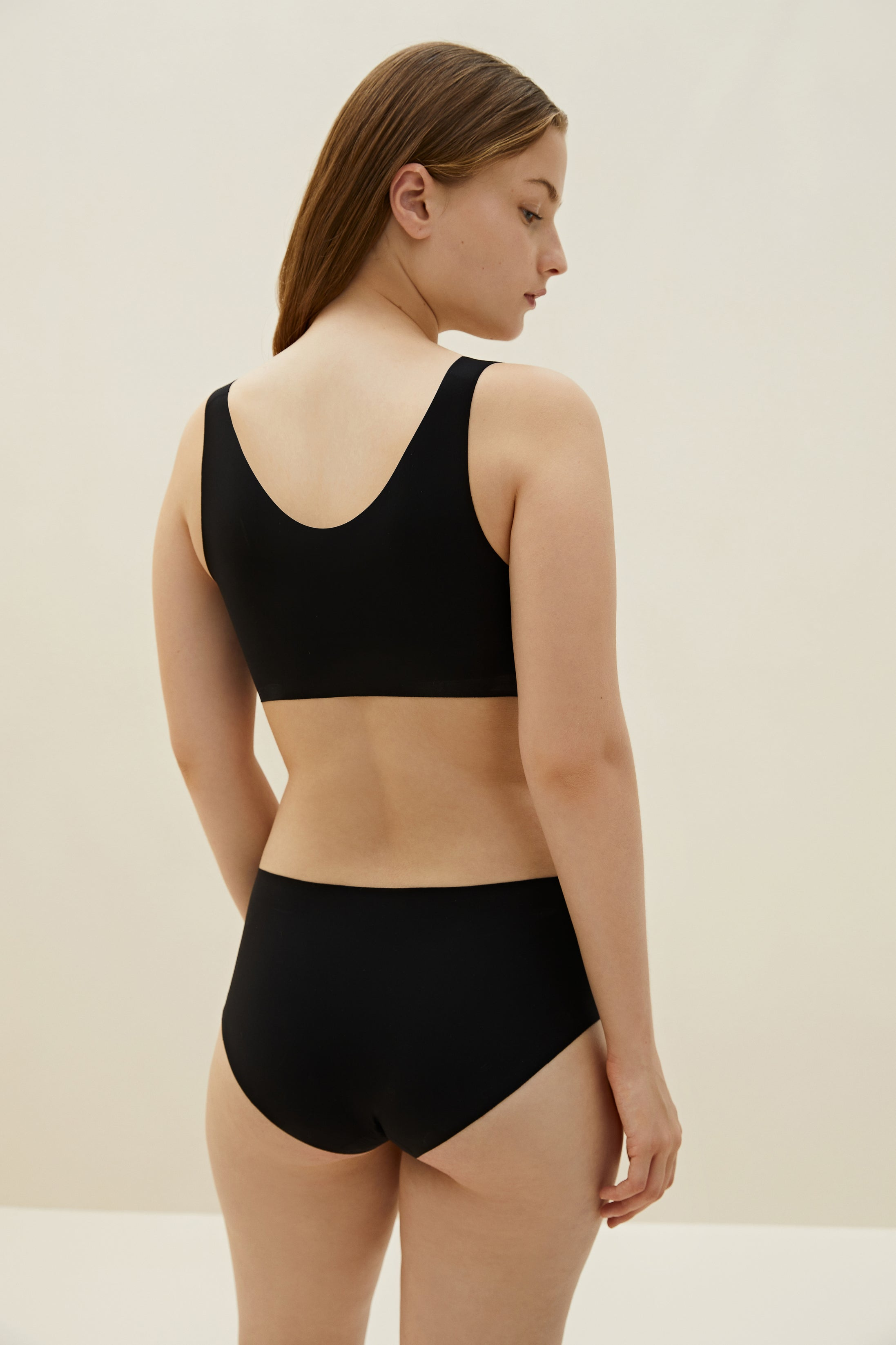 Model wearing NEIWAI's Barely Zero bra and brief set in black.