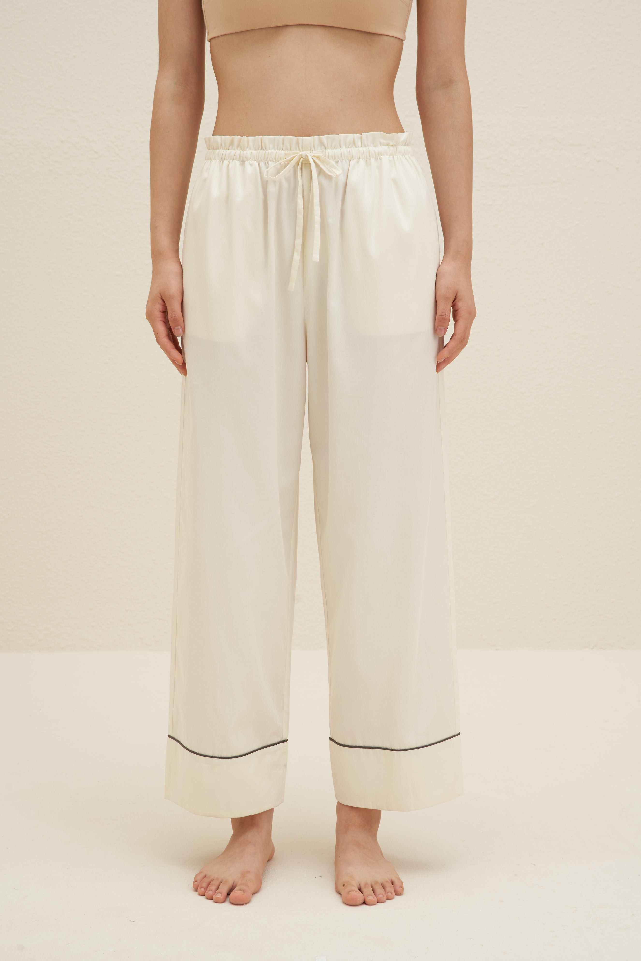 Model wearing NEIWAI's Classic Embroidered Straight Leg Pajama Pants in Pristine.