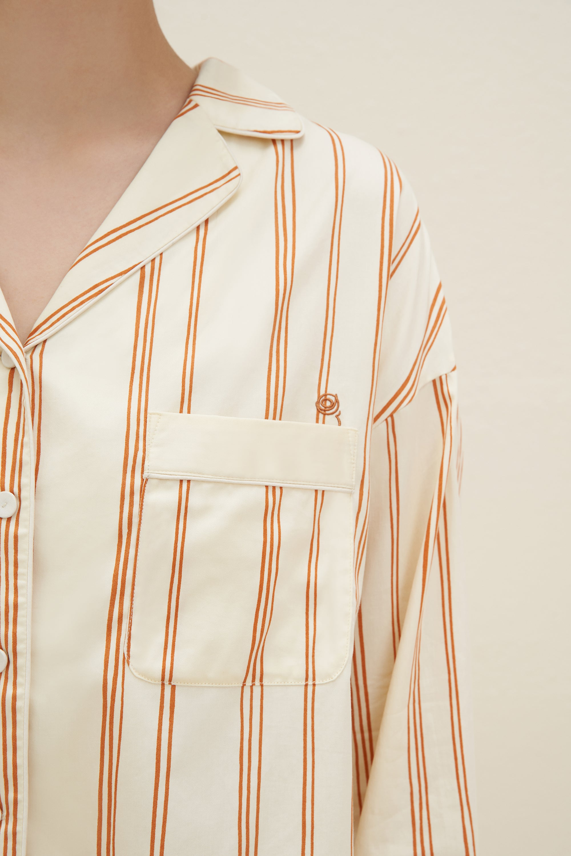 Model wearing NEIWAI's Classic Embroidered Pajama Shirt in Orange Lattice.