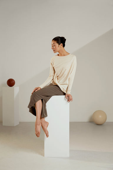 Model wearing NEIWAI's Boundless Asymmetrical Long-Sleeve Tee in Egret.