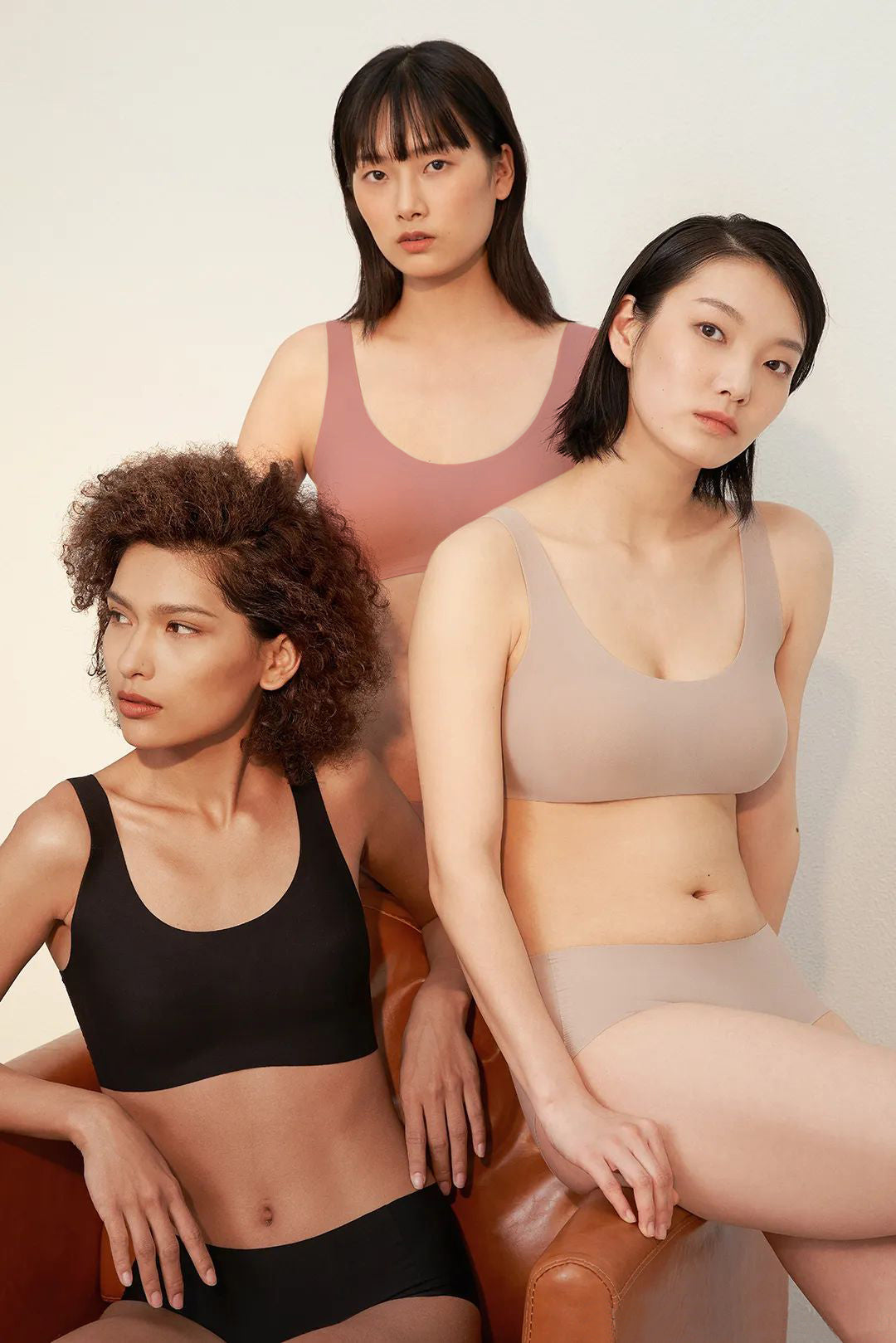 Models wearing NEIWAI's Barely Zero bra and brief set in black, nude, and coral..
