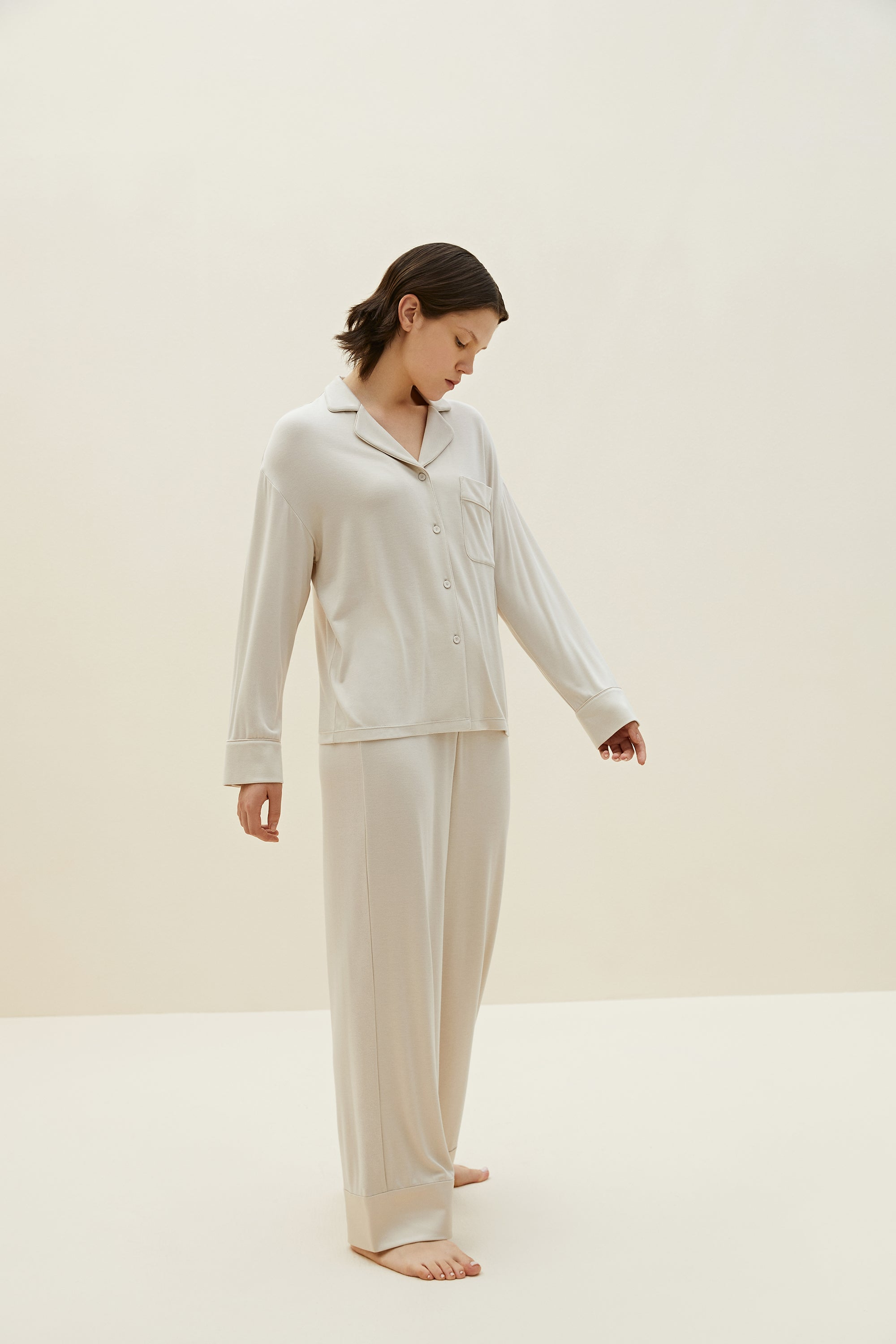 Model wearing NEIWAI's Classic Cozy Button-Up Pajama Top in Light Gray.