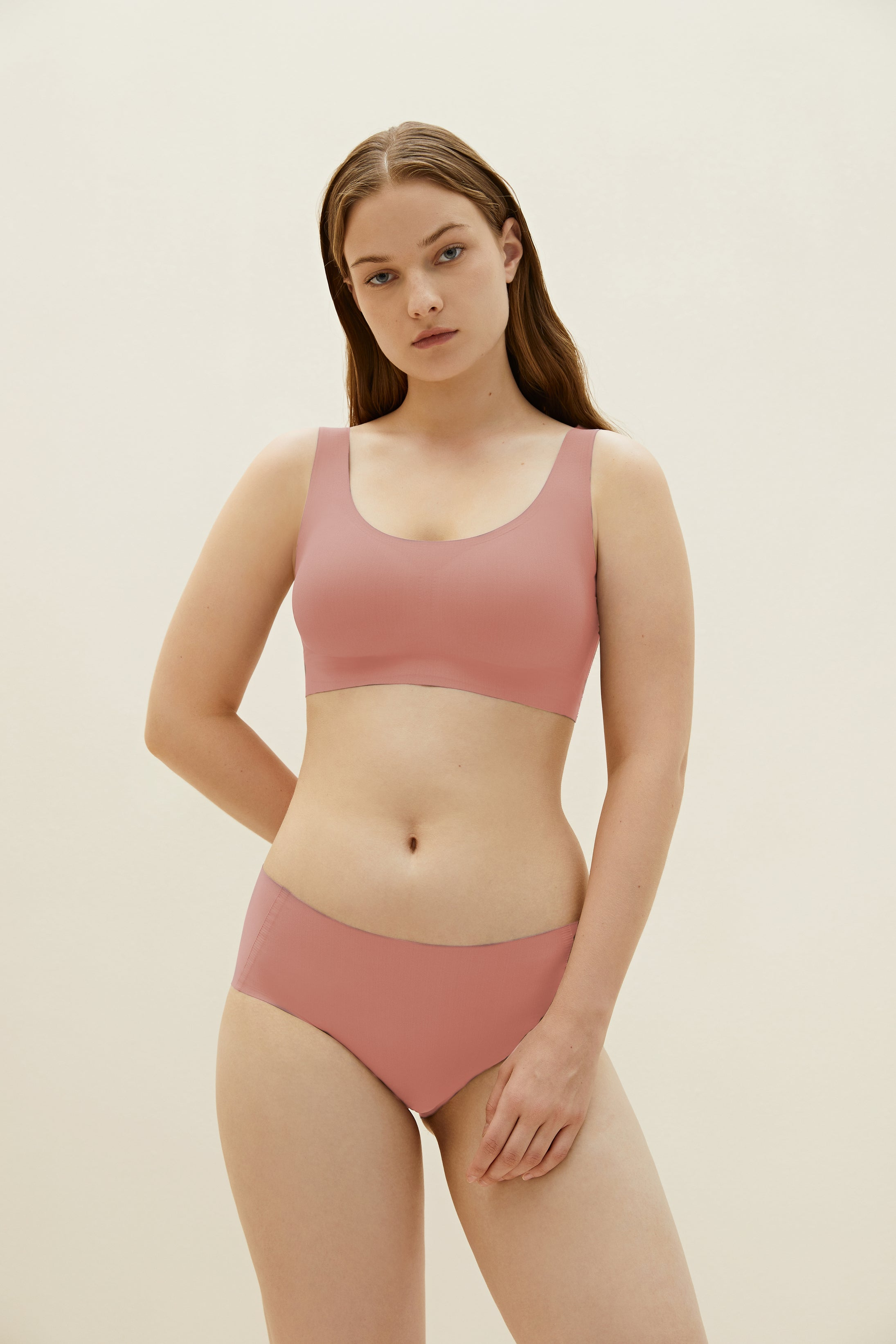 Model wearing NEIWAI's Barely Zero bra and brief set in coral.