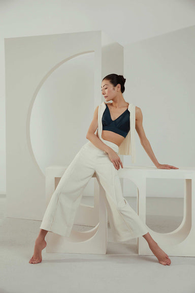 Yuan Yuan Tan modeling the NEIWAI ACTIVE x Yuan Yuan Tan Satin V Neck Sports Bra in Bluesteel.