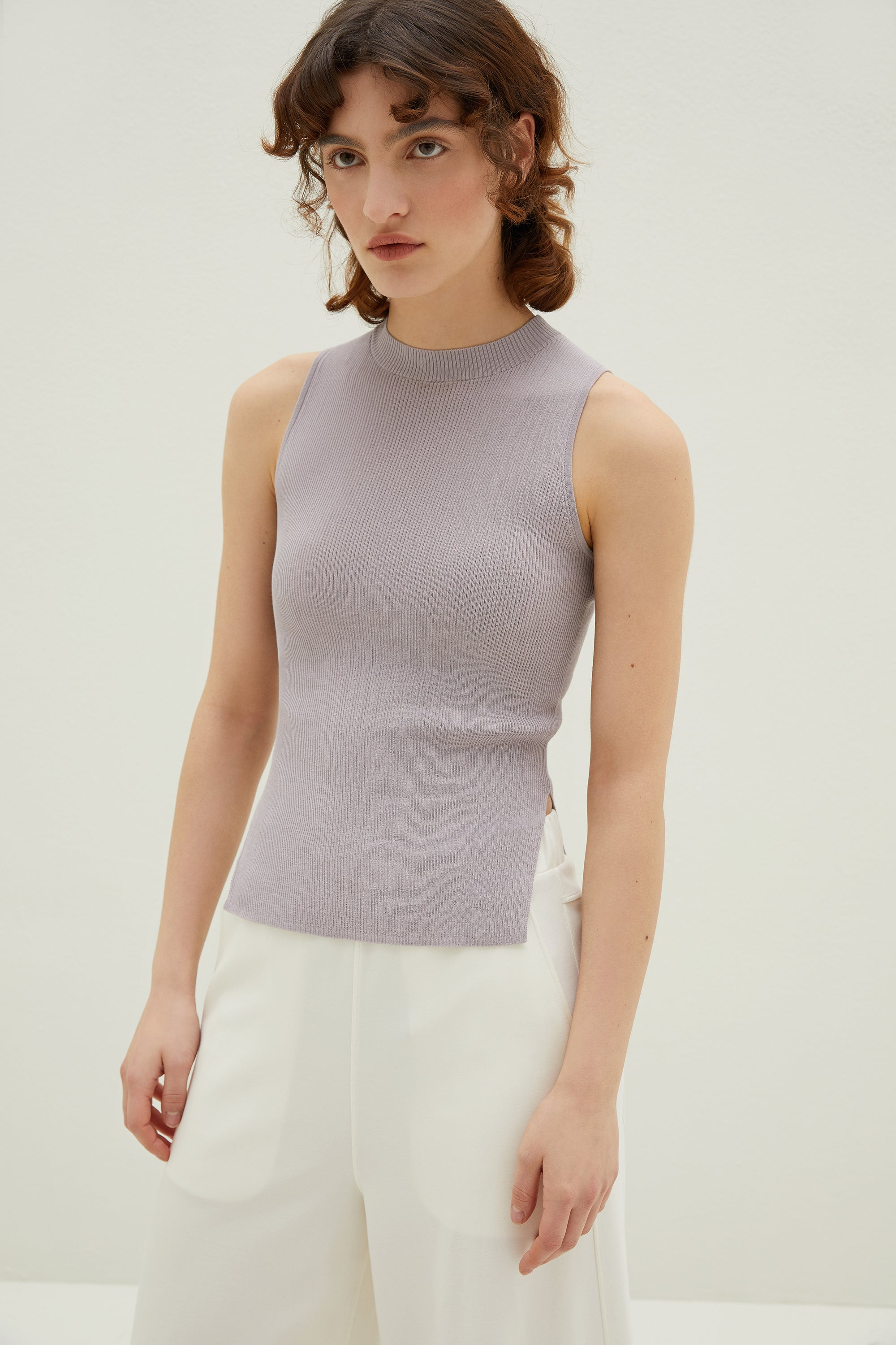 Model wearing NEIWAI's Knitted Sleeveless Mock Neck Tank Top in Serenity.