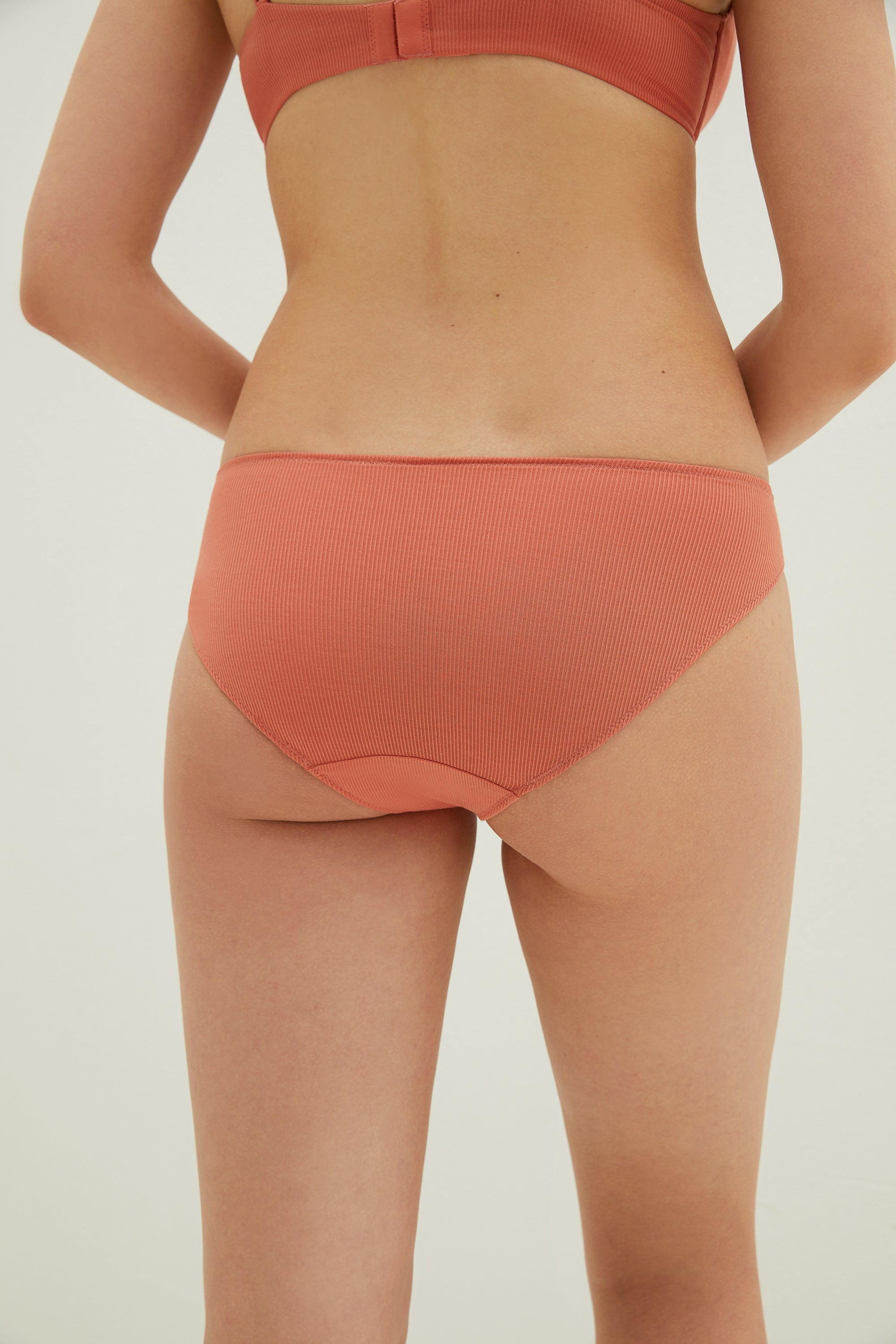 Model wearing NEIWAI's Pure Beauty V-shape TENCEL™ Low Waist Brief in Orange.
