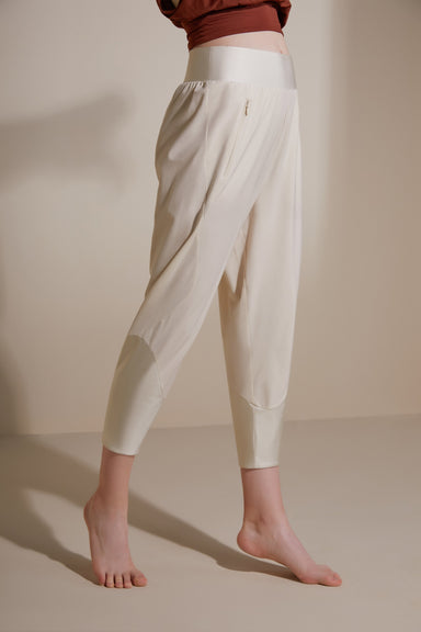 Model wearing the NEIWAI ACTIVE x Yuan Yuan Tan Satin Splicing Sweatpants in Egret.