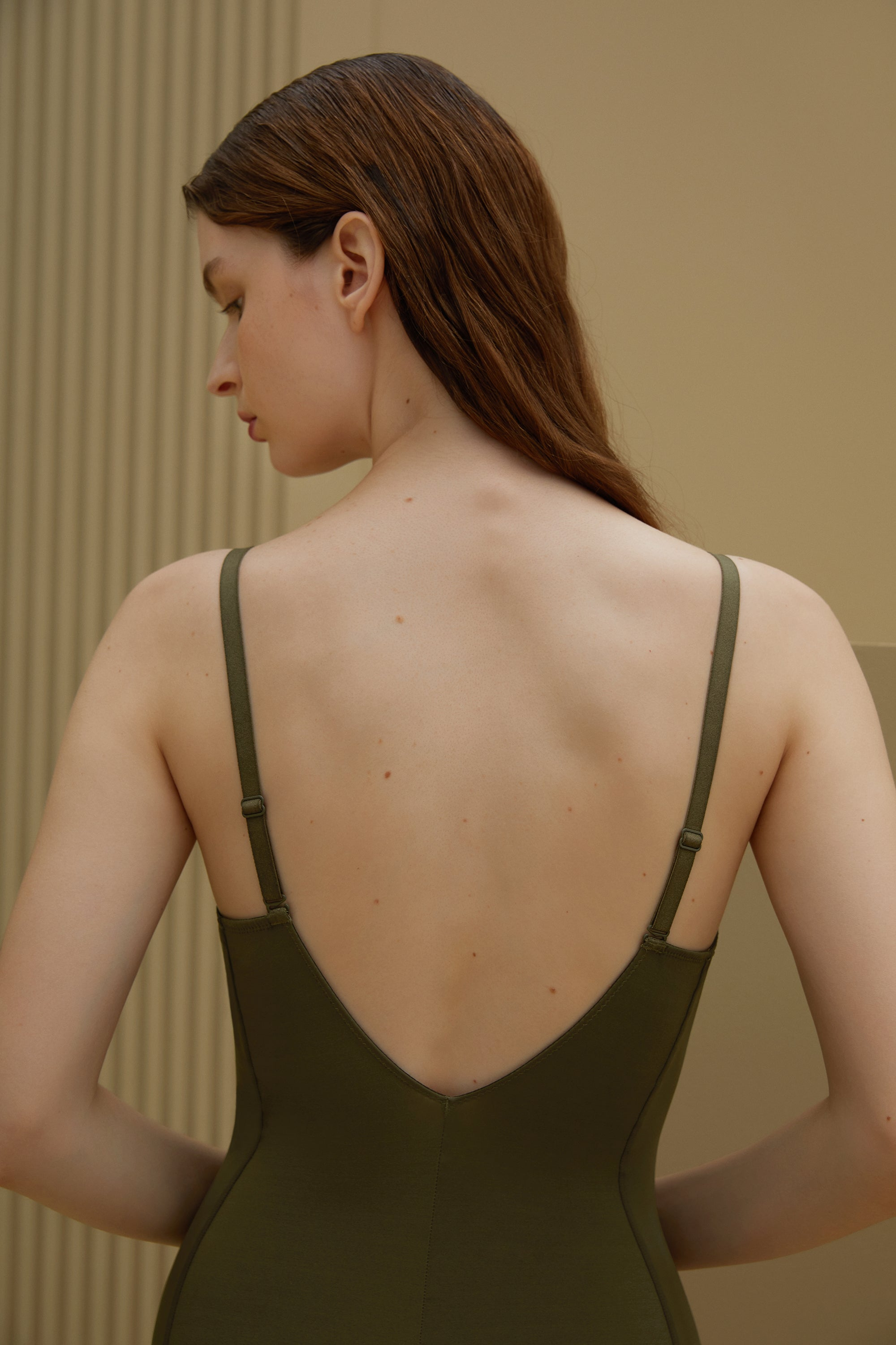 Model wearing NEIWAI's Pure Beauty Matte Plunged V-back Bodysuit in Olive.