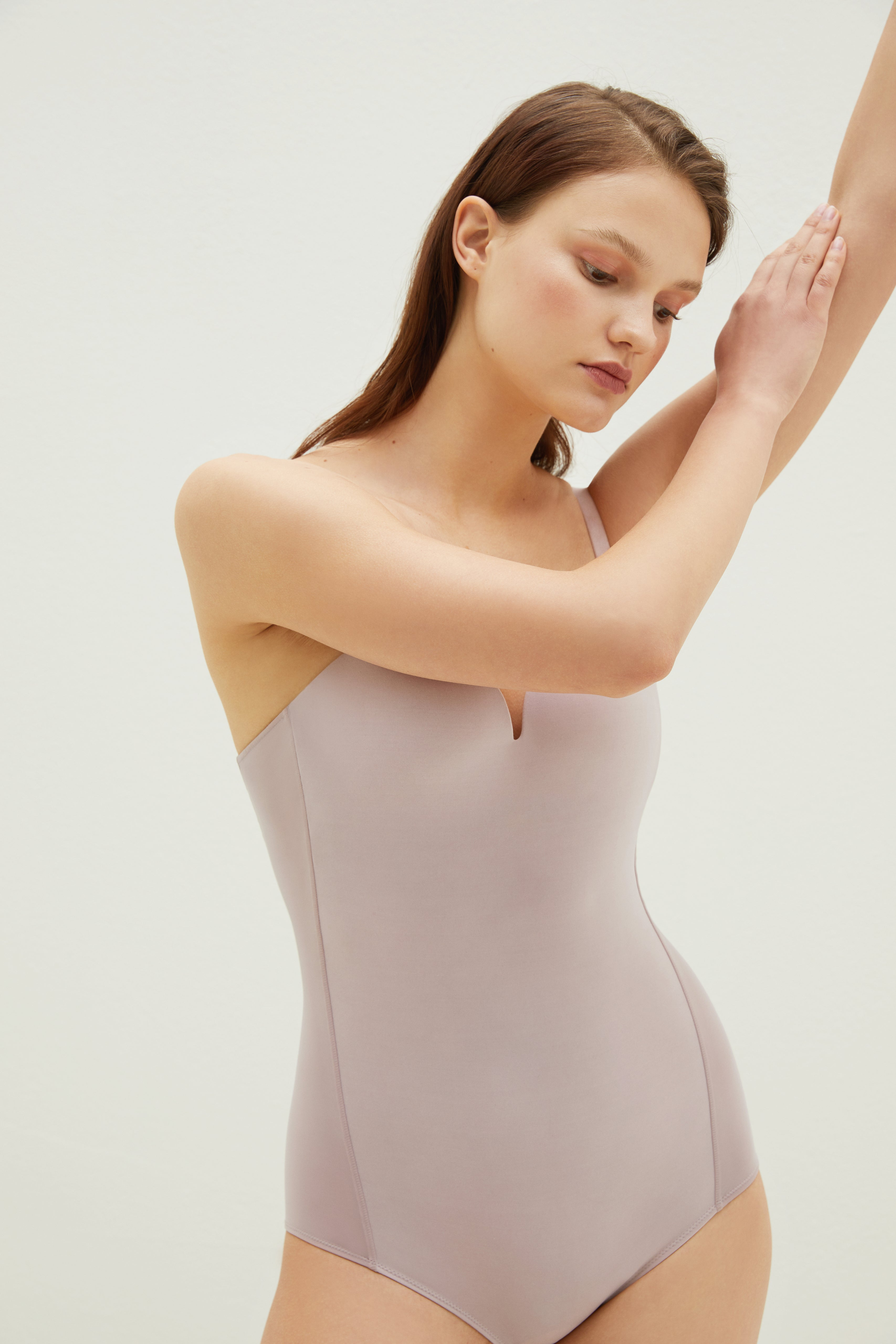 Model wearing NEIWAI's Pure Beauty Matte Plunged V-back Bodysuit in Lilac Ash.