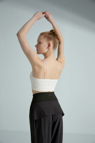 Model wearing the NEIWAI ACTIVE x Yuan Yuan Tan Sling Pleated Sports Bra in White.