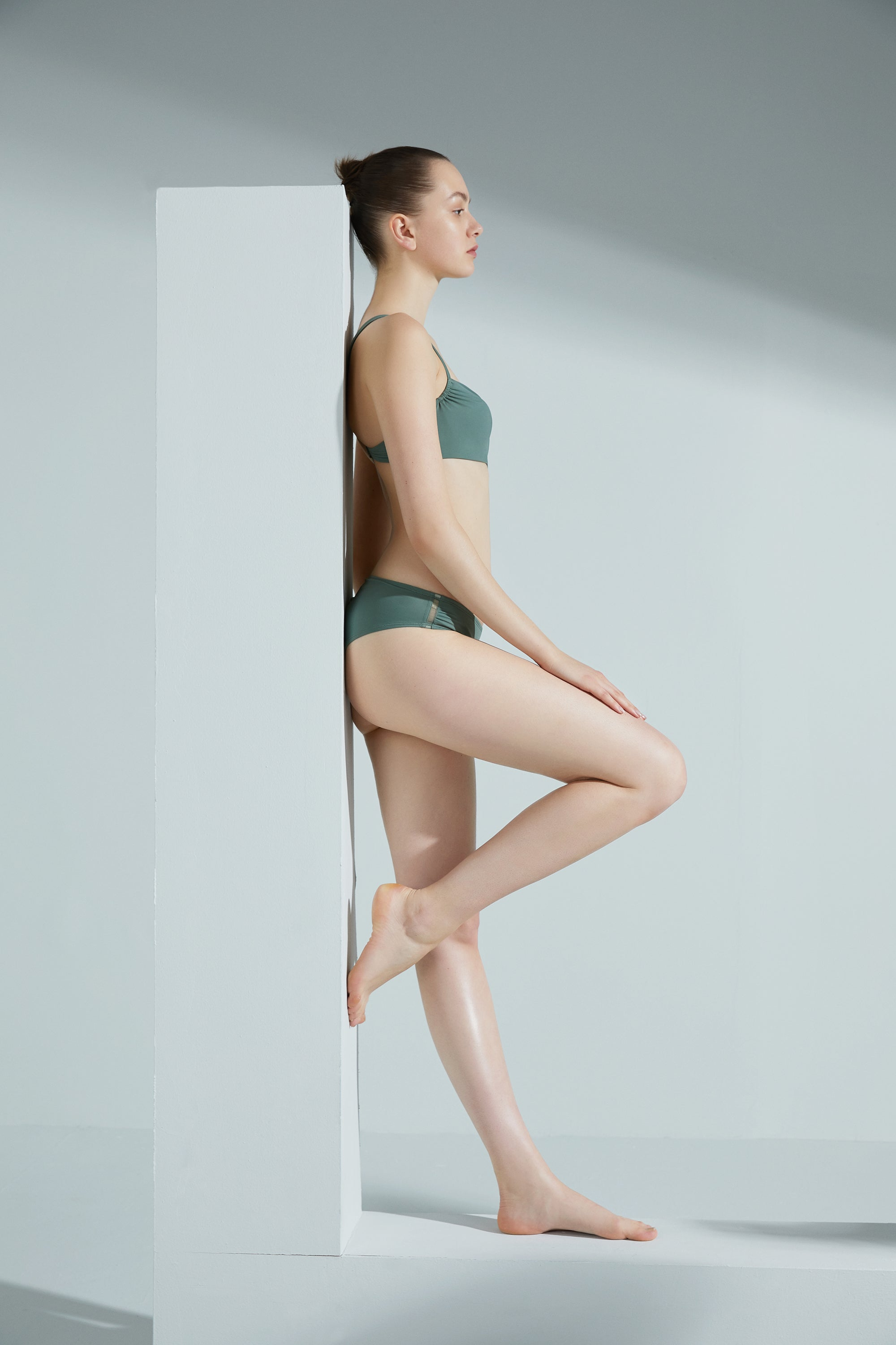Model wearing NEIWAI's Voyage 1/2 Cup Bandeau Bikini Top in Sagebrush Green.