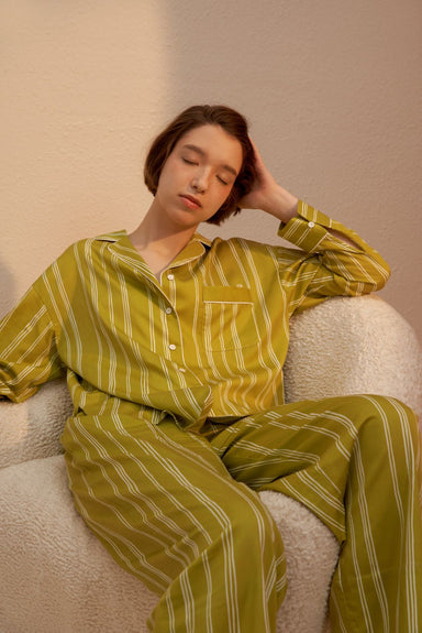 Model wearing NEIWAI's Classic Embroidered Pajama Shirt in Olive Lattice.