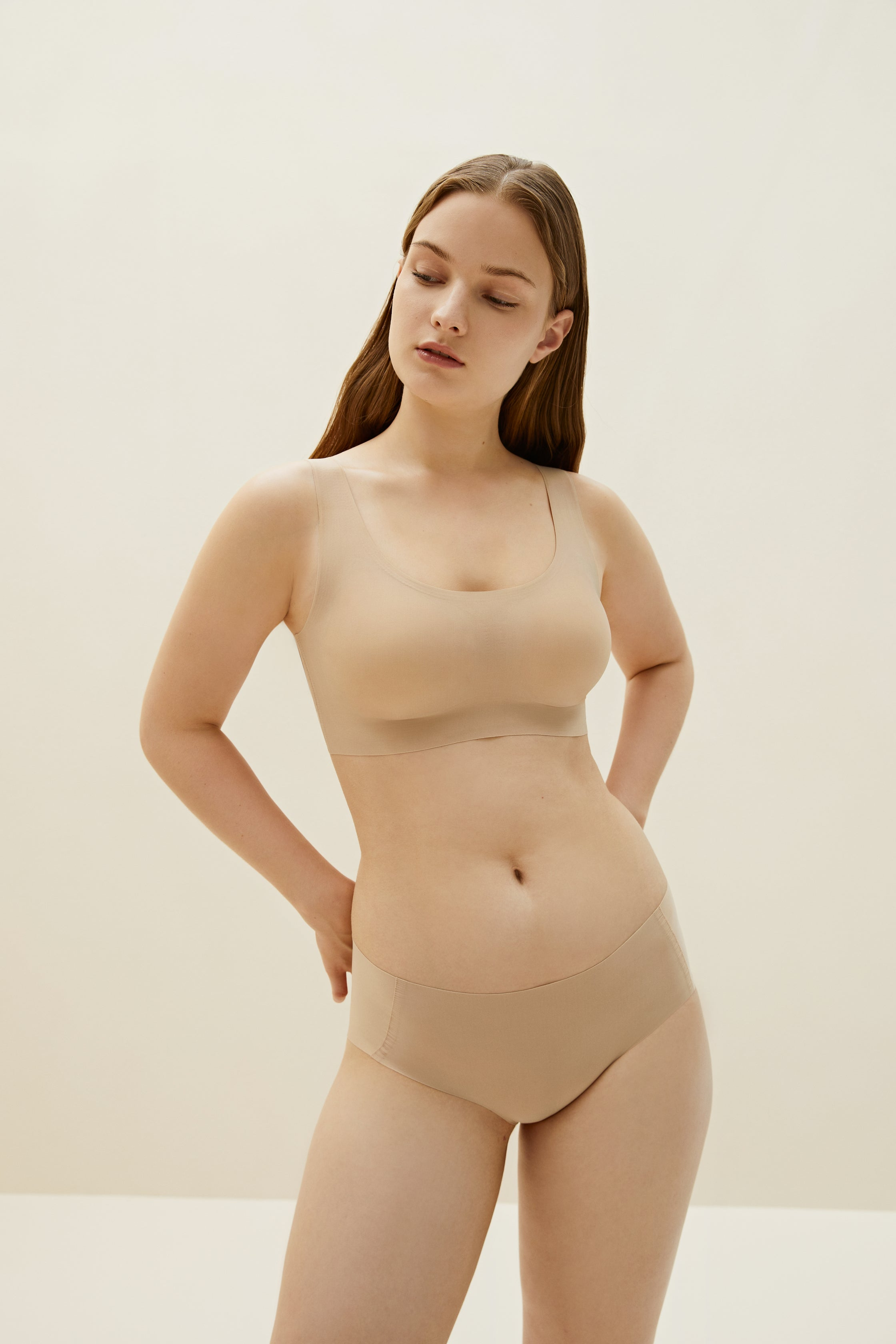 Model wearing NEIWAI's Barely Zero bra and brief set in nude color.