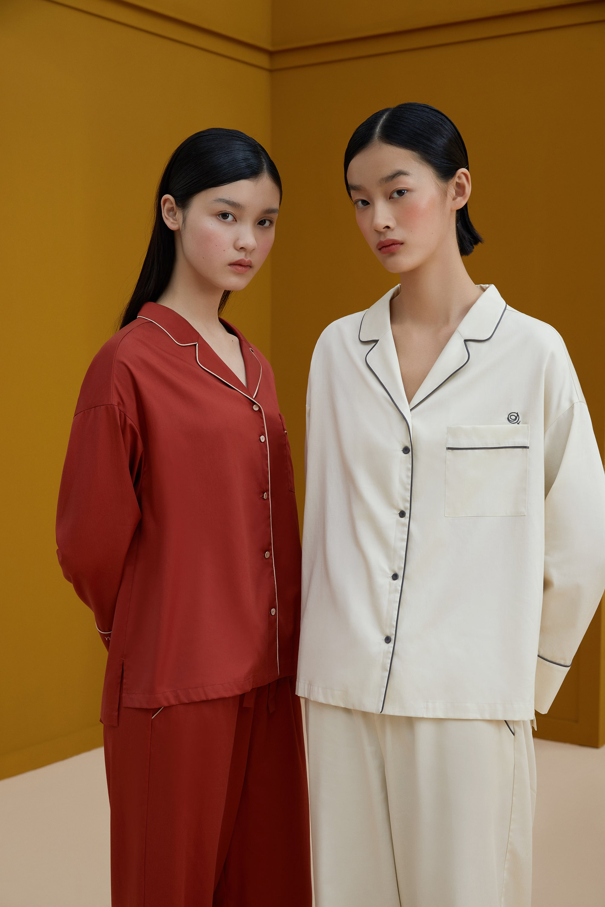 Models wearing NEIWAI's Classic Embroidered Pajama Shirt in Baked Clay (left) and Pristine (right).