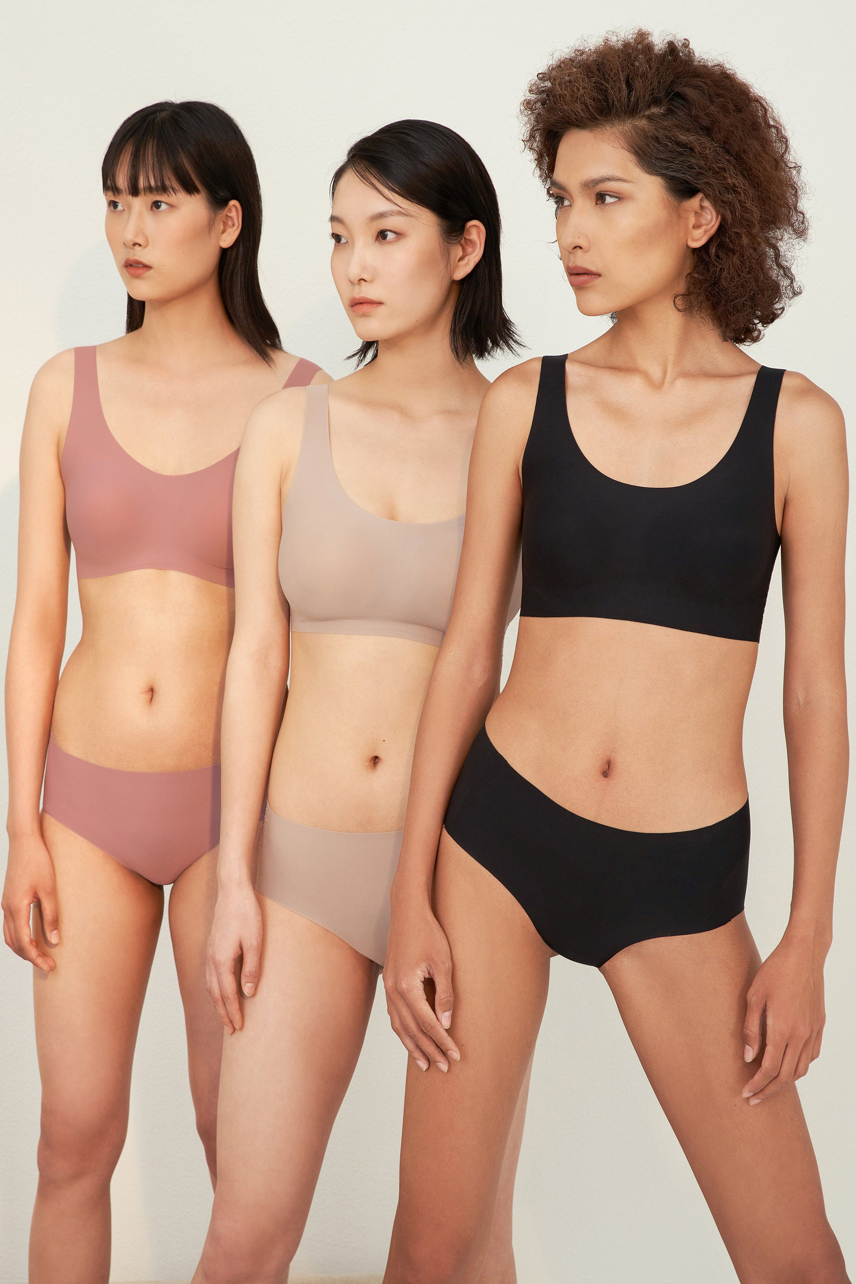 Models wearing NEIWAI's Barely Zero bra and brief set in coral, nude, and black.