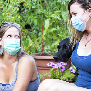 2 girls in masks with dog