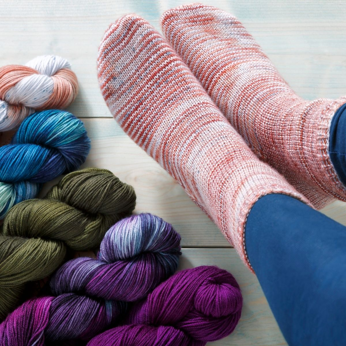 A woman's feet  are pictured, wearing hand knit socks in Manos del Uruguay Alegria. The colorway of the socks is Colorado river, additional skeins of yarn are shown.