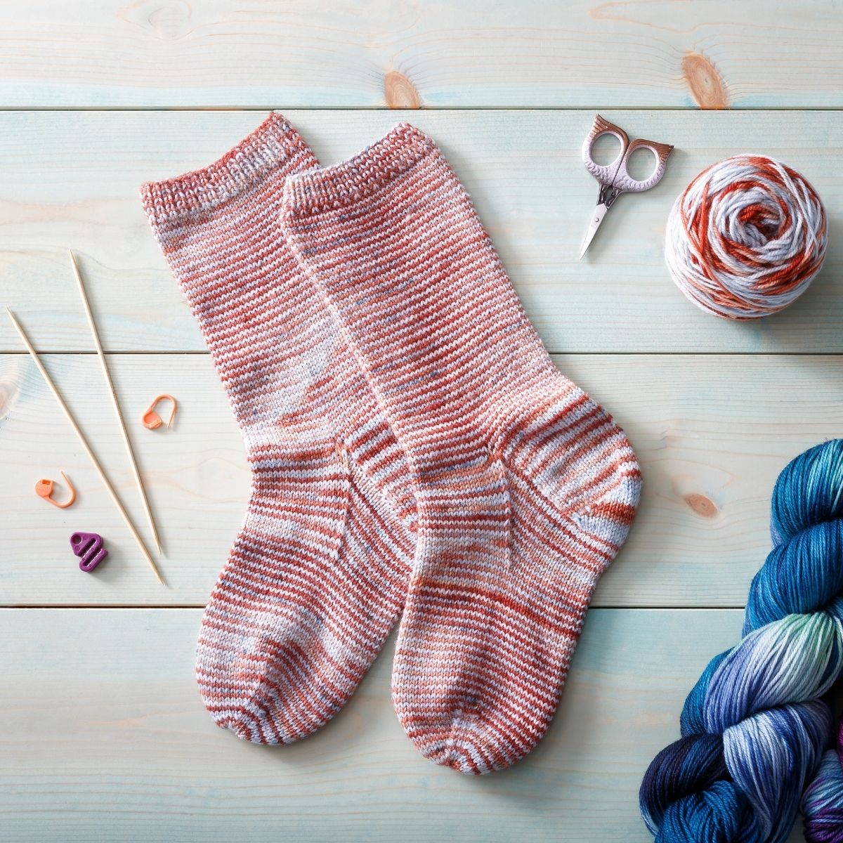 A pair of socks knit in Manos Del Uraguay Alegria, colorway Colorado River, laid flat on a wooden surface. Scissors, knitting notions and yarn surround the socks.