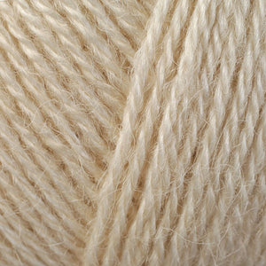 Skein of Berroco Folio DK weight yarn in the color Orr (Cream) for knitting and crocheting.