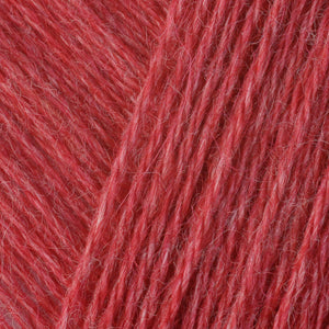 Skein of Berroco Folio DK weight yarn in the color Tomato (Red) for knitting and crocheting.