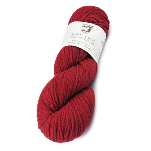 Skein of Juniper Moon Farms Santa Cruz Worsted weight yarn in the color Saffron (Red) for knitting and crocheting.