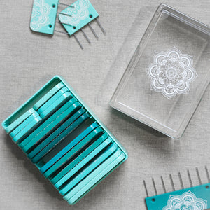 A set of light turquoise blocking pins printed with mindful Mandalas by Knitter's Pride makes blocking knit and crochet projects easy.