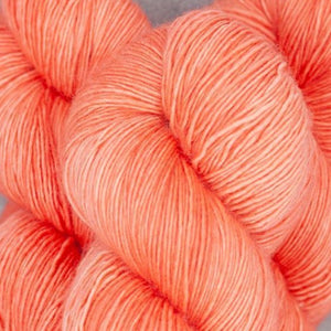 Skein of Madelinetosh A.S.A.P. Super Bulky weight yarn in the color Grapefruit (Orange) for knitting and crocheting.