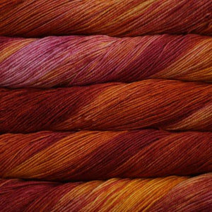 Skein of Malabrigo Arroyo Sport weight yarn in the color Flama (Red) for knitting and crocheting.