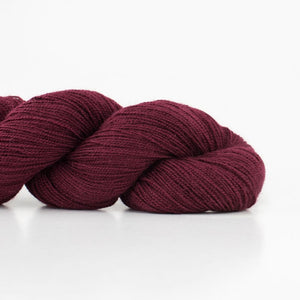 Skein of Shibui Cima Lace weight yarn in the color Bordeaux (Red) for knitting and crocheting.