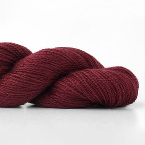 Skein of Shibui Lunar Lace weight yarn in the color Bordeaux (Red) for knitting and crocheting.