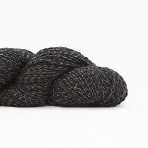 Skein of Shibui Nest DK weight yarn in the color Abyss (Black) for knitting and crocheting.