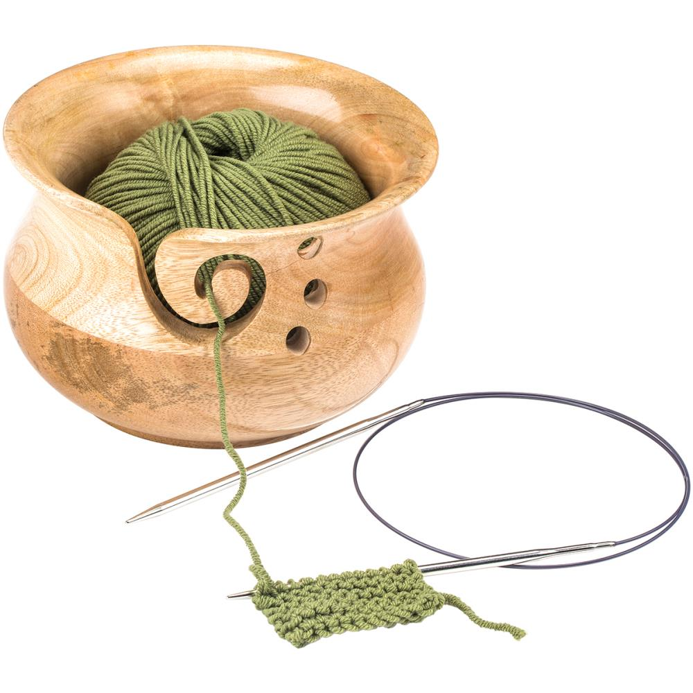 Susan Bates Mangowood Yarn Bowl holding green yarn on a knitting needle