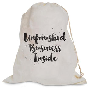 "White muslin bag with graphic ""Unfinished Business Inside"" for knitting or crochet projects."
