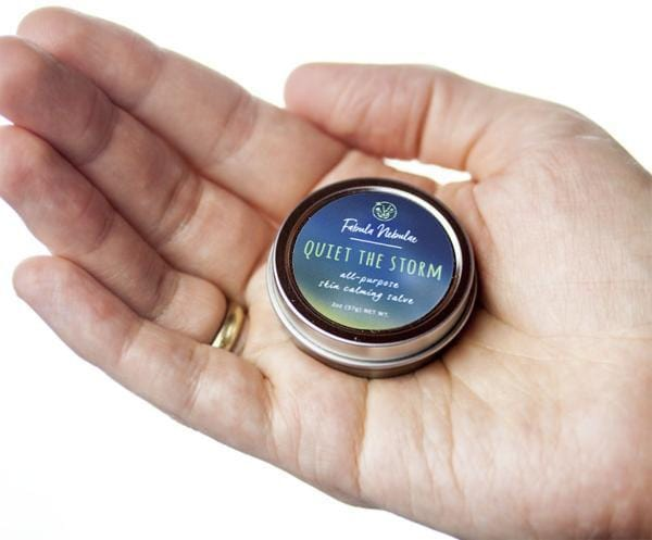 A tin of Quiet the Storm salve held in hand