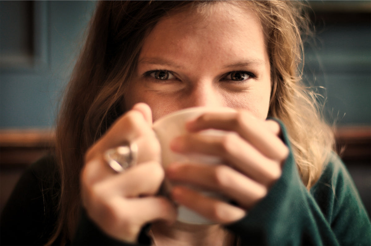 woman drinking from mug smiling with ring wearing jumper