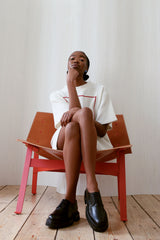 Youthful brown skinned woman sitting in wide chair with legs crossed against white background.