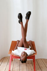 Youthful brown skinned woman sitting upside down in wide chair with legs crossed in the air against a white background.