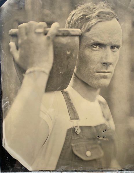 tin type photo of man carrying a vessel