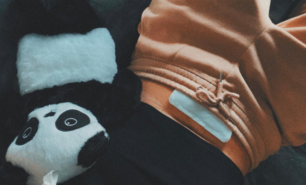 A stomach with a heat patch on and Panda teddy
