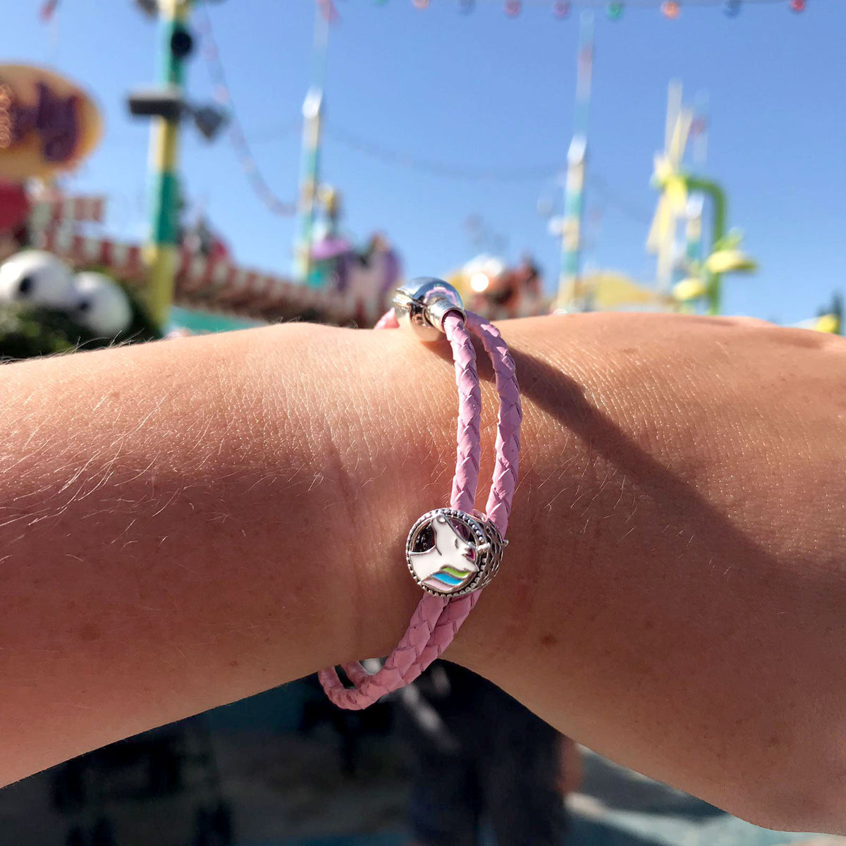 Close up of a wrist, showing a Pink rope bracelet and a Silver Unicorn charm