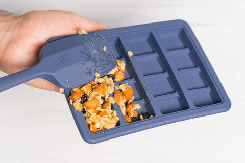 Spooning Kind Bar Mix into Magical Granola Mold with Magical Spatula