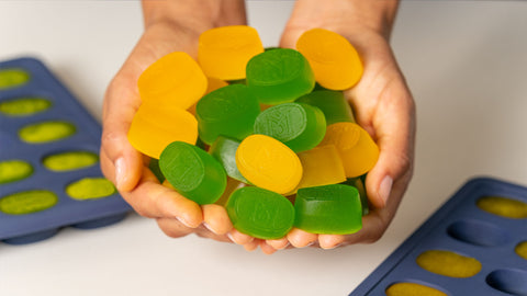 Hands Holding Mango and Lime Gummies