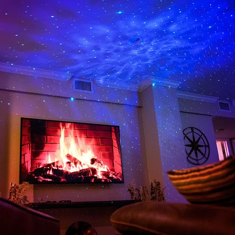 Galaxy Star Nebula Light Projector projecting blue neba light on the ceiling of a living room with fire burning in fireplace