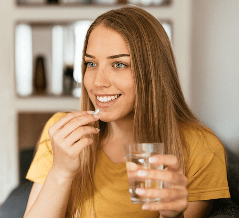 a woman with smile holds a bottle of water and eats capsules