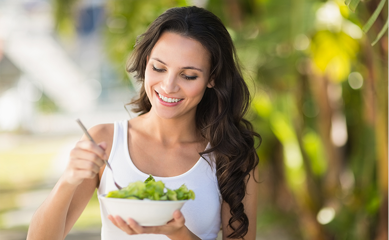a women with smile on her face eating salad