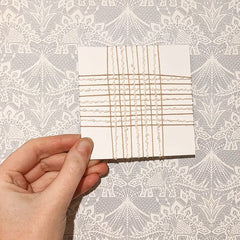 4 inch card woven with cream textured and ivory yarn in a loose square weave.