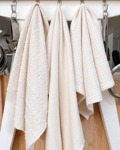 Three kitchen towels hung on hooks.